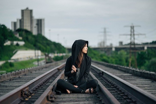 a lady sit on railway think for the investment in asia